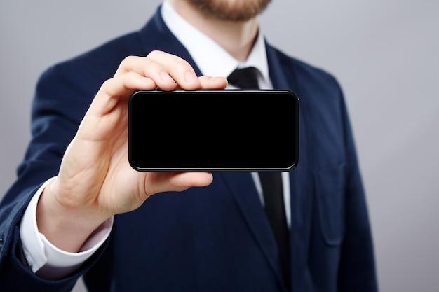 흰 셔츠와 양복 벽을 입고 노동자의 손을 가까이, 비즈니스 개념, 휴대 전화를 보여주는 조롱.