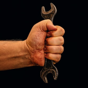 Worker's hand with open-end wrench isolated on black