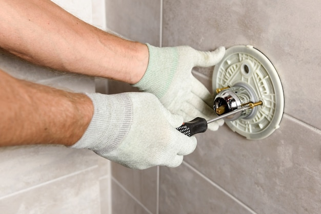 The worker's hands are mounting a built-in faucet.