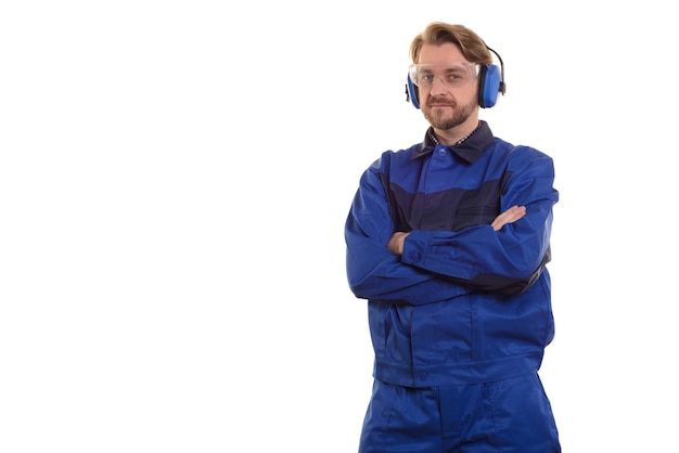 Worker in safety glasses and headphones stands with his arms crossed