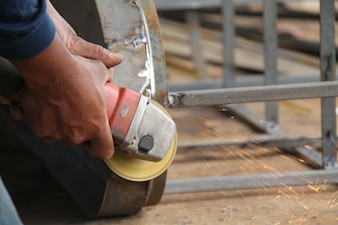 Worker sawing metal with a grinder, sparks fly