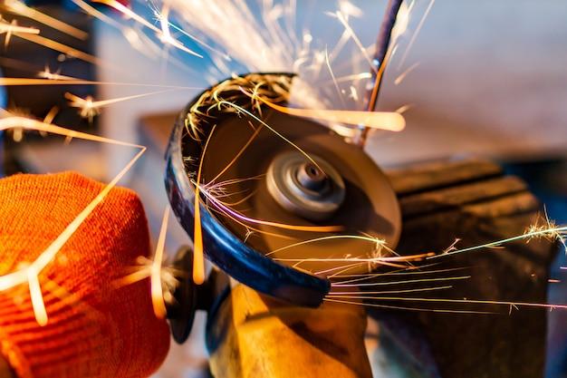 작업자가 전기 톱으로 금속을 톱질하면 많은 불꽃이 기구에서 날아갑니다.