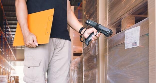 商品のラベルが付いたバーコードスキャナーをスキャンする労働者。倉庫在庫管理のためのコンピュータ機器。