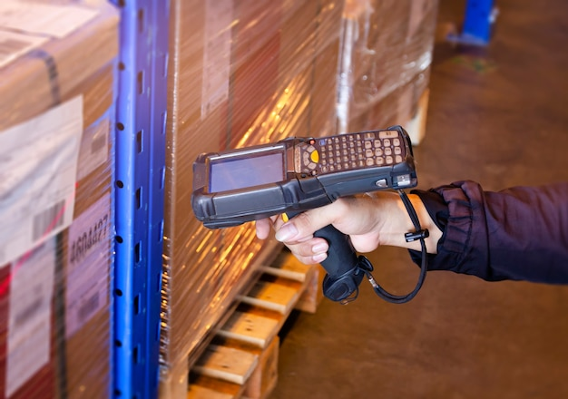 Worker scanning bar code scanner with package boxes warehouse inventory mangement
