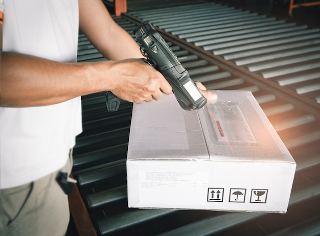 Worker scanning barcode scanner with shipment boxes on conveyor belt.