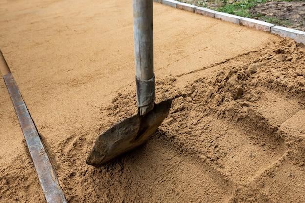 작업자가 포장용 슬래브를 놓기 위해 수평으로 모래 깔개를 스크리딩합니다.