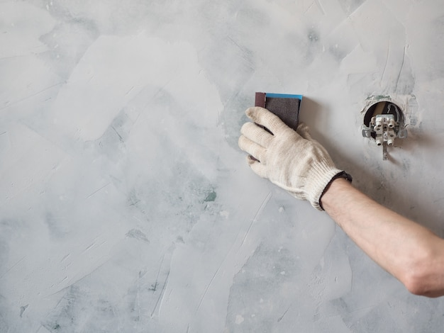 Worker scrubbing the wall with sandpaper and prepare the surface for painting. repair and renovation at home. new interior design.