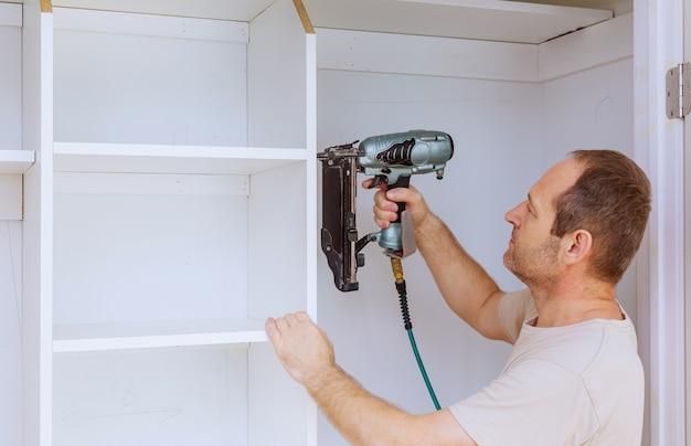 Worker sets the shelf for closet cabinet