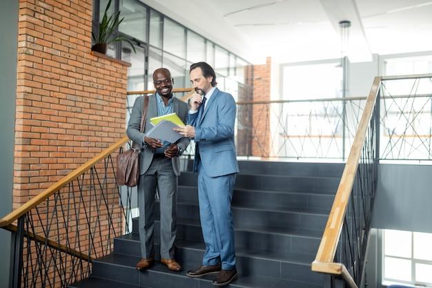 웃는 노동자. 상사와 이야기하고 회의를 논의하면서 웃고있는 검은 피부의 부지런한 회사원