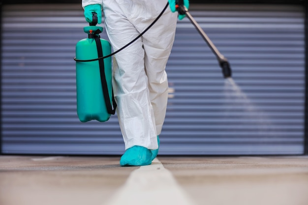 Worker spraying with disinfectant during corona outbreak.