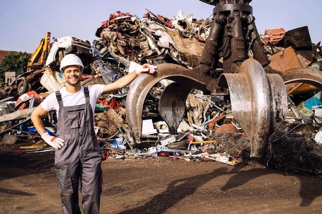 폐차장에서 고철 부품을 들어 올리는 데 사용되는 유압 산업 기계 옆에 서 있는 작업자