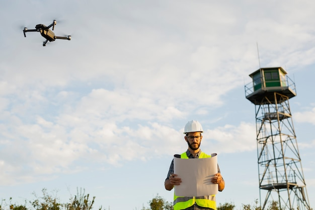 Worker standing and checking his plans next to a flying drone