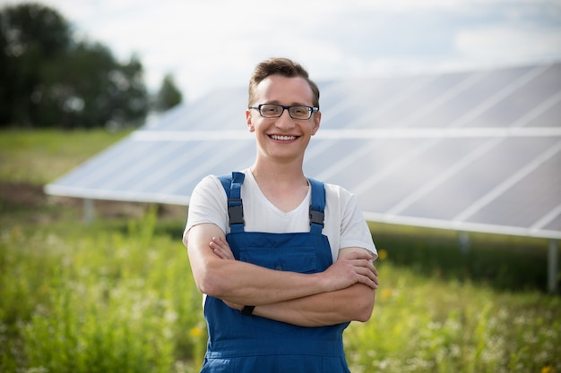 Worker standing in the field with solar with solar panels on backstage.