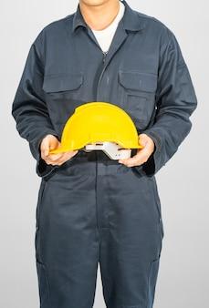 Рабочий, стоящий в синем комбинезоне, держит желтый шлем, изолированный на сером фоне