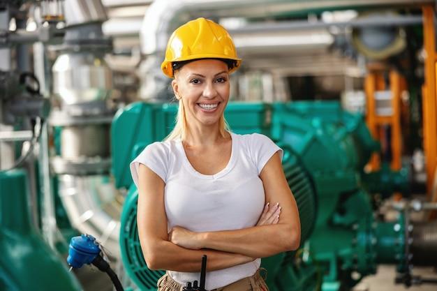 Рабочий стоял со скрещенными руками на теплоцентрали.