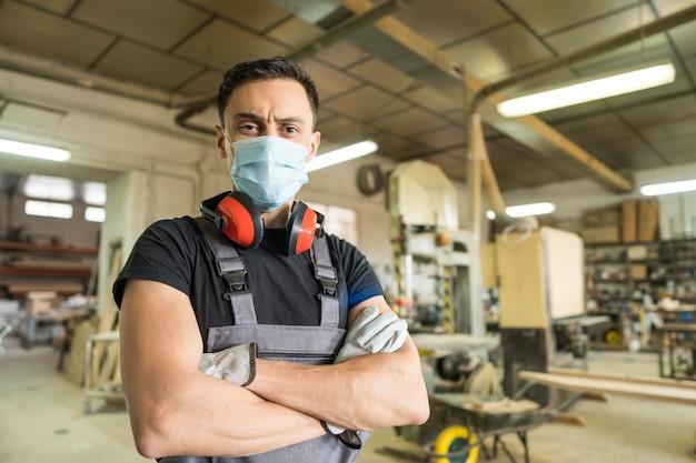 Рабочий, стоящий с маской и защитным снаряжением, глядя на камеру, улыбаясь на фабрике. средний выстрел.