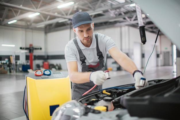 작업자는 차체의 열린 앞 부분에 선다. 그는 엔진에 연결하기위한 전원 코드를 가지고 있습니다.