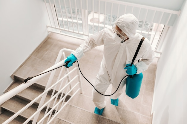 Worker in sterile uniform, with gloves and facial mask sterilizing railing in school.