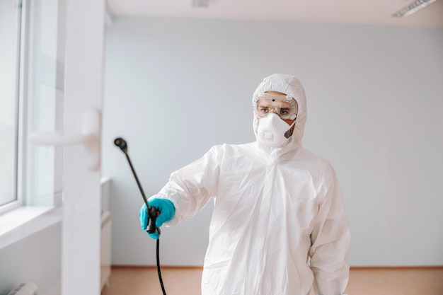 Worker in sterile uniform, with mask and gloves spraying with disinfectant window in school.