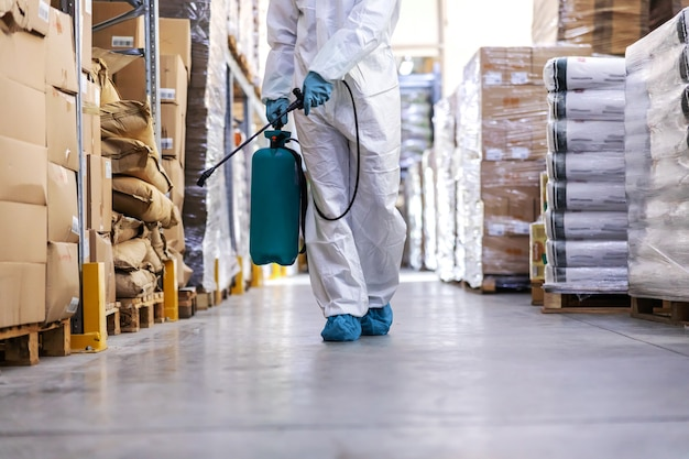 Worker in sterile uniform with rubber gloves holding sprayer with disinfectant and spraying around warehouse. corona outbreak concept.