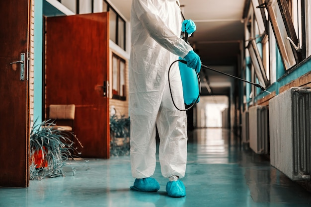 Worker in sterile uniform, with rubber gloves holding sprayer with disinfectant and spraying school hallway.