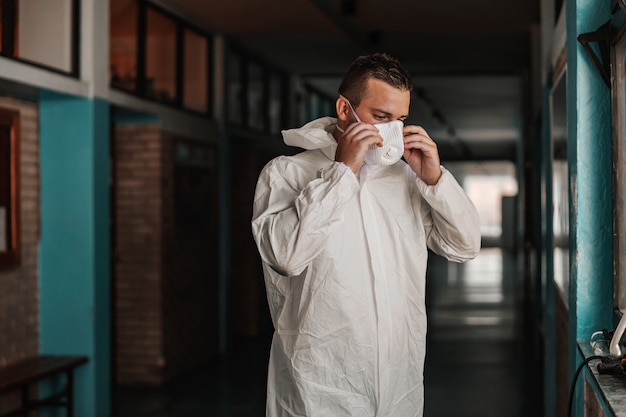 Worker in sterile white uniform taking off mask while standing in hallway in school after disinfecting.