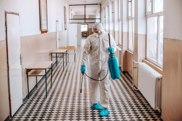 Worker in sterile white uniform, with mask and glasses holding sprayer with disinfectant and spraying around hallway in school. prevention of spreading corona virus.