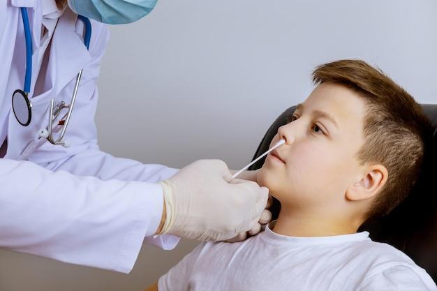 健康診断のための鼻のサンプルのために綿棒を取っている労働者コロナウイルスcovid-19テストテスト男の子の健康診断のための鼻のサンプル。