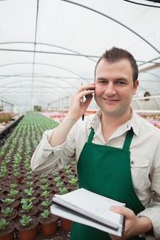 温室でノートと電話をしている労働者