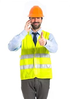 Рабочий разговаривает с мобильным телефоном
