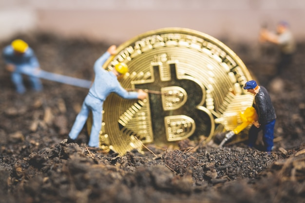 Worker team digging ground to uncover big shiny bitcoin