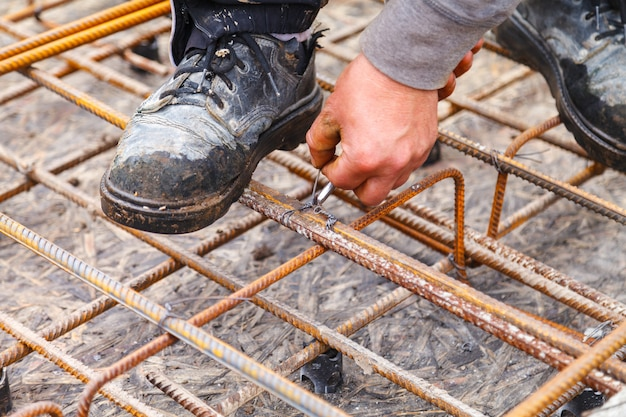 Worker ties steel reinforcing bars with wire.