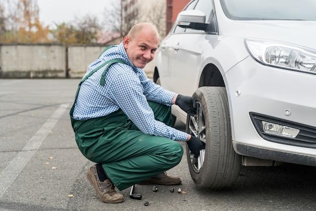 Worker in uniform fixing changed wheel in car