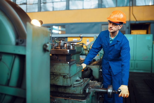 Worker in uniform and helmet works on lathe, factory. industrial production, metalwork engineering, manufacturing