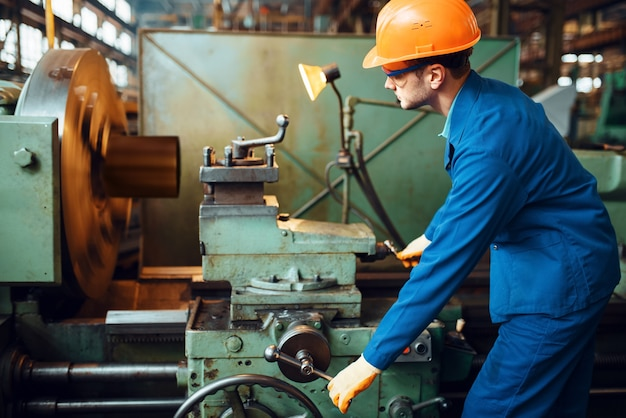 Worker in uniform and helmet works on lathe, factory. industrial production, metalwork engineering, power machines manufacturing