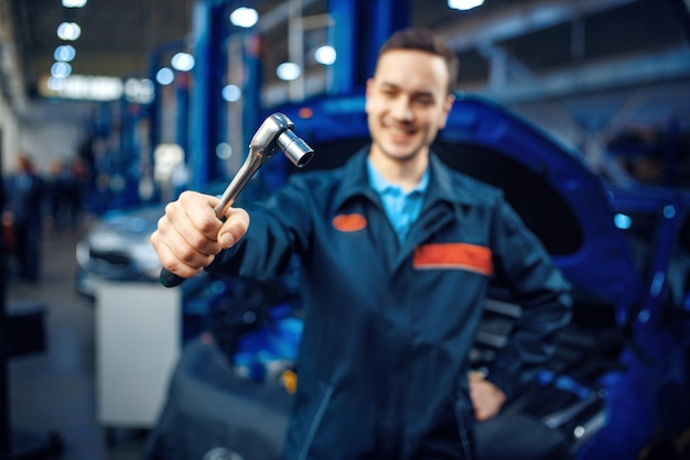 Worker in uniform holds wrench, vehicle with opened hood, car service station.