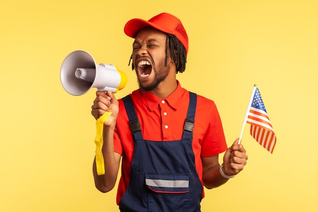 Worker in uniform with beard and dreadlocks holding usa flag screaming at loudspeaker protesting