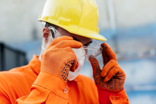 Worker in uniform with hard hat and protective glasses