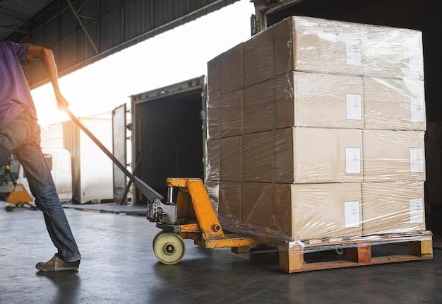 Рабочий, выгружающий упаковочные коробки изнутри грузового контейнера логистика и транспорт