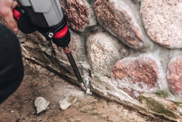 Рабочий использует электродрель по бетону (отбойный молоток). дробление бетона или камня.