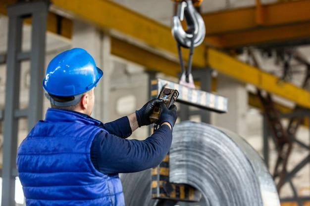 Работник использует управляющий джойстик на заводе