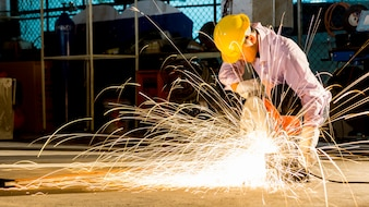 Worker uses grinding cut metal, focus on flash light line of sharp spark