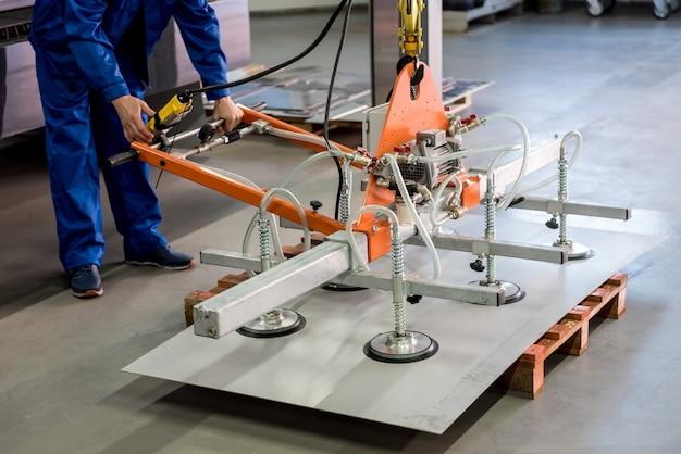 Рабочий использует присоски для транспортировки больших листов металла.