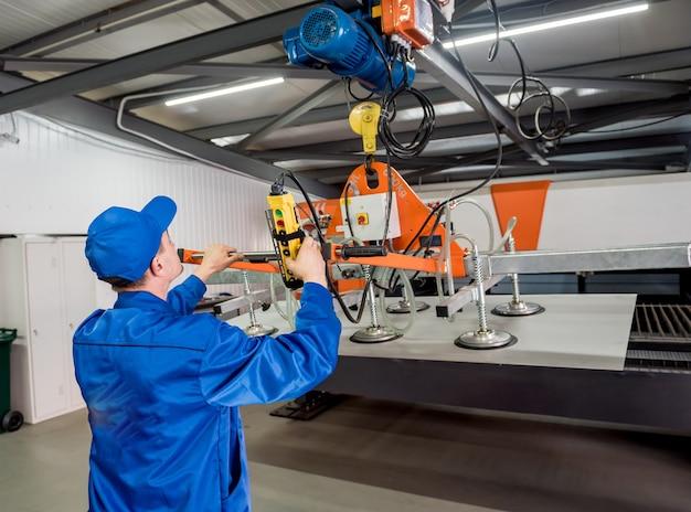 労働者は大きな金属板を運ぶために吸盤を使用します
