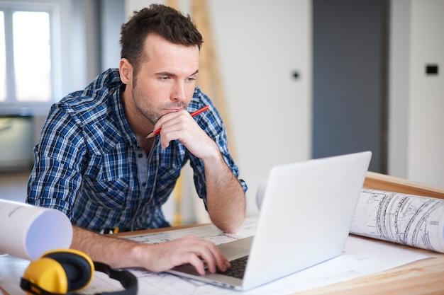Рабочий, использующий ноутбук в офисе