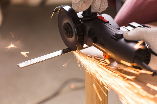 공장에서 앵글 그라인더를 사용하고 불꽃을 던지는 작업자.