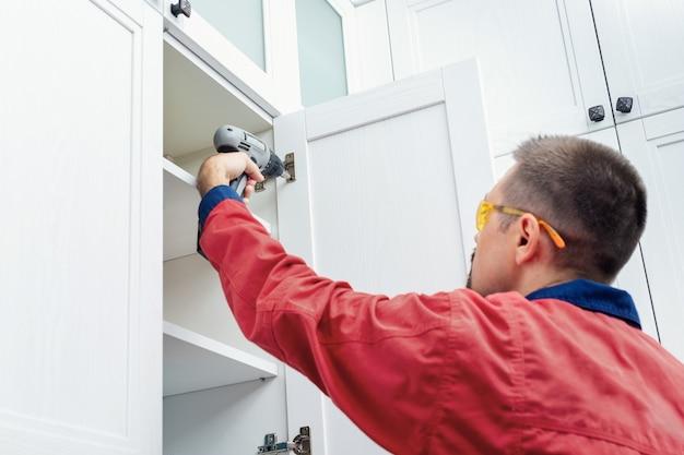 주방에 새 가구를 설치하는 동안 무선 드라이버를 사용하는 작업자