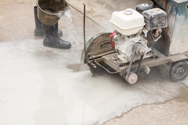 建設現場でコンクリート道路を切断するダイヤモンド鋸刃機を使用する労働者