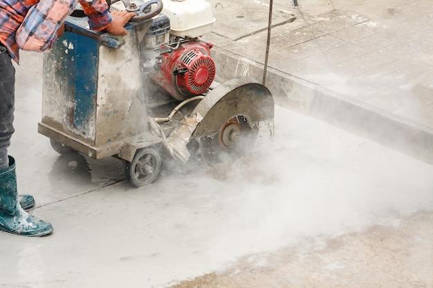 Рабочий с алмазной пилой режет бетонную дорогу на строительной площадке