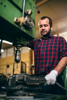 Работник, используя сверлильный станок на заводе